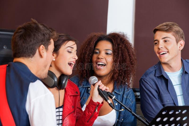 Sångare med musikbandmedlemmar i inspelningstudio royaltyfri fotografi