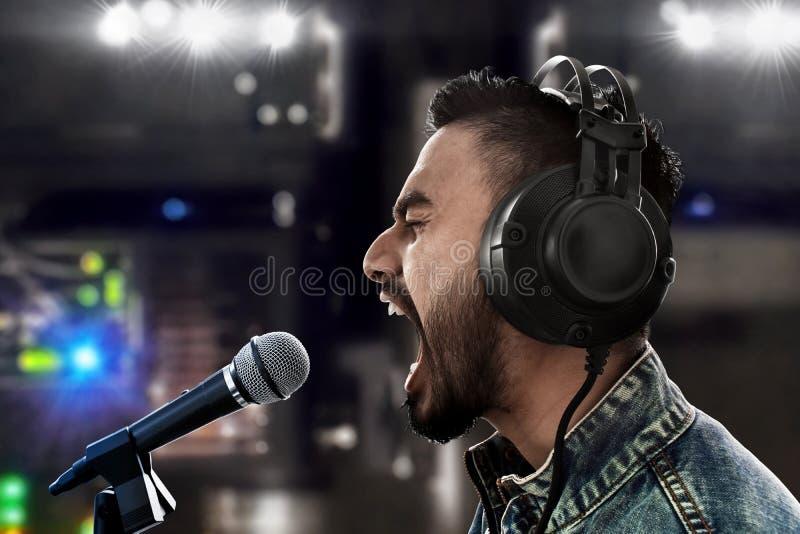 Sångare som antecknar en sång i musikstudio royaltyfria bilder