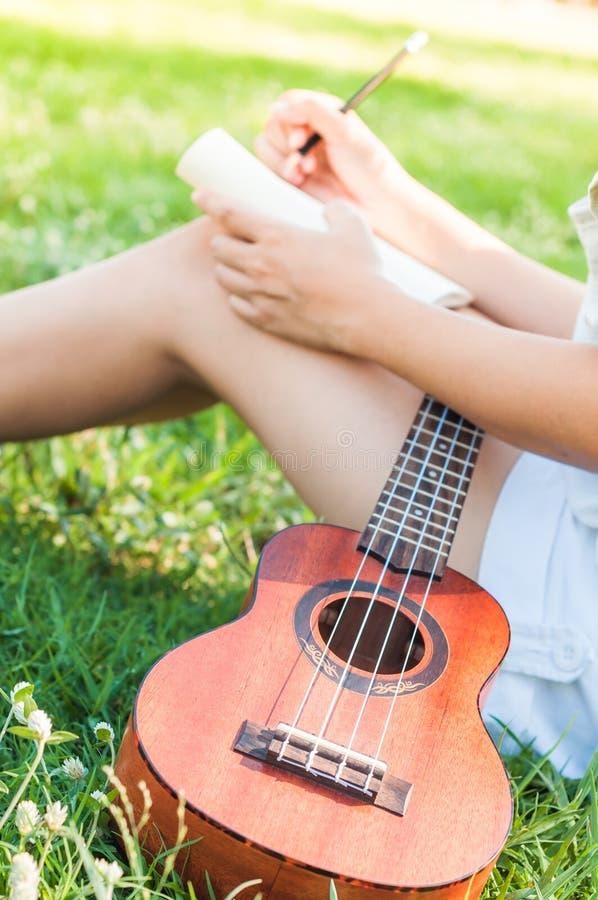 Sångförfattare med den lilla gitarren royaltyfri foto