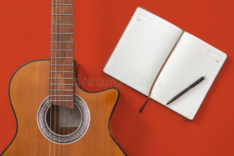 Sångförfattaretabell en workspace med den akustiska gitarren för musiker och notepadpapper royaltyfri bild