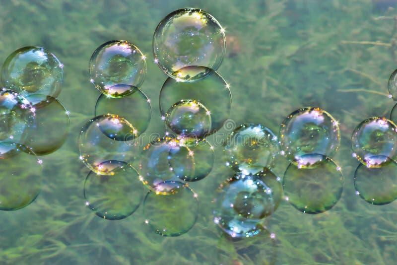 Såpbubblor på vatten arkivfoton
