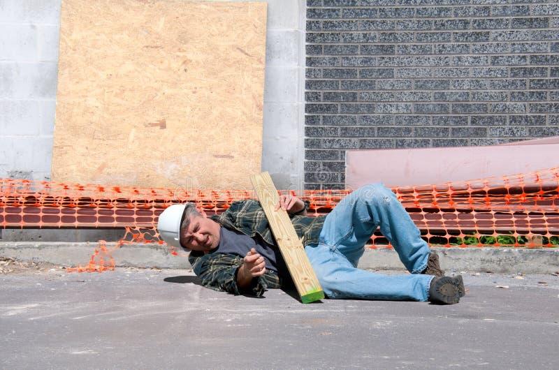 Sårad byggnadsarbetare på arbetsplatsen royaltyfri bild