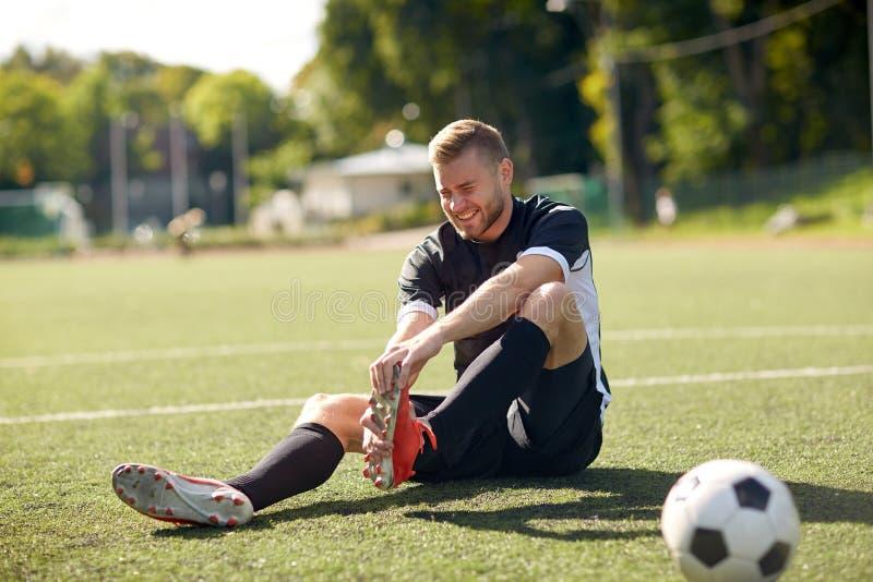 Sårad fotbollspelare med bollen på fotbollfält arkivbild