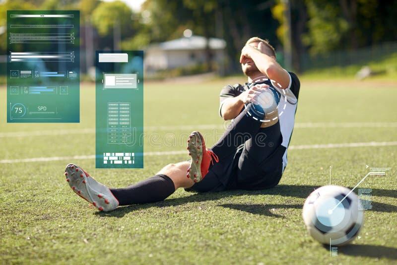 Sårad fotbollspelare med bollen på fotbollfält royaltyfri fotografi