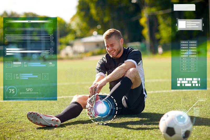 Sårad fotbollspelare med bollen på fotbollfält arkivfoton