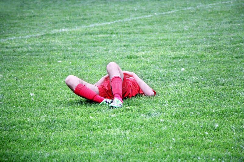 Sårad fotbollsspelare eller fotboll arkivbild