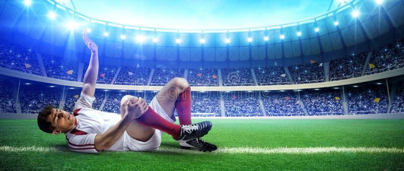 Sårad fotbollsspelare på stadionfält arkivfoto