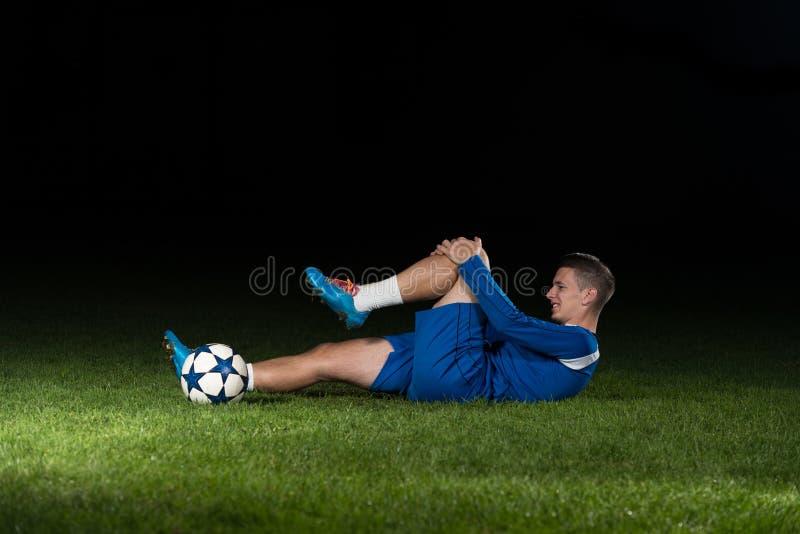 Sårad fotbollsspelare som ligger på jordningen arkivfoton