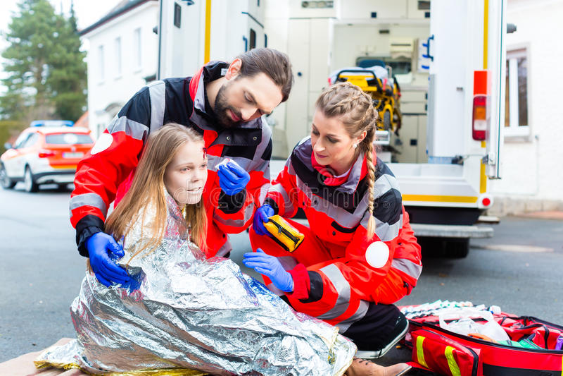 Sårad kvinna för ambulansdoktorsportion royaltyfria bilder