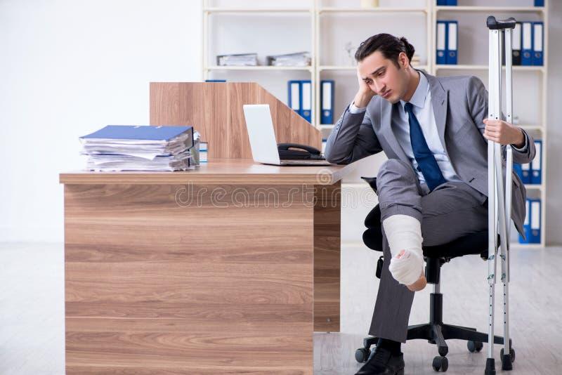 Sårad manlig anställd för ben i kontoret fotografering för bildbyråer