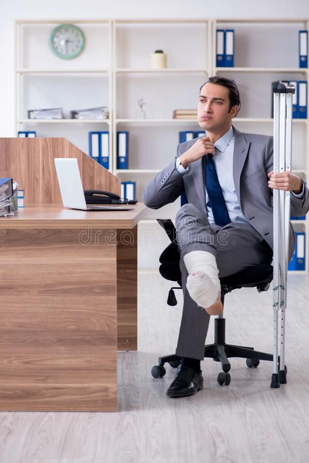 Sårad manlig anställd för ben i kontoret arkivbilder