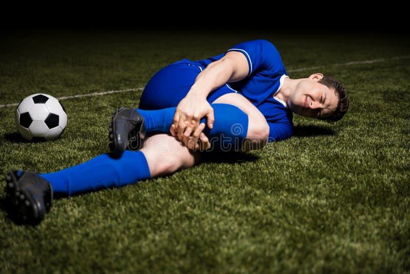 Sårad manlig fotbollspelare på fält royaltyfri bild