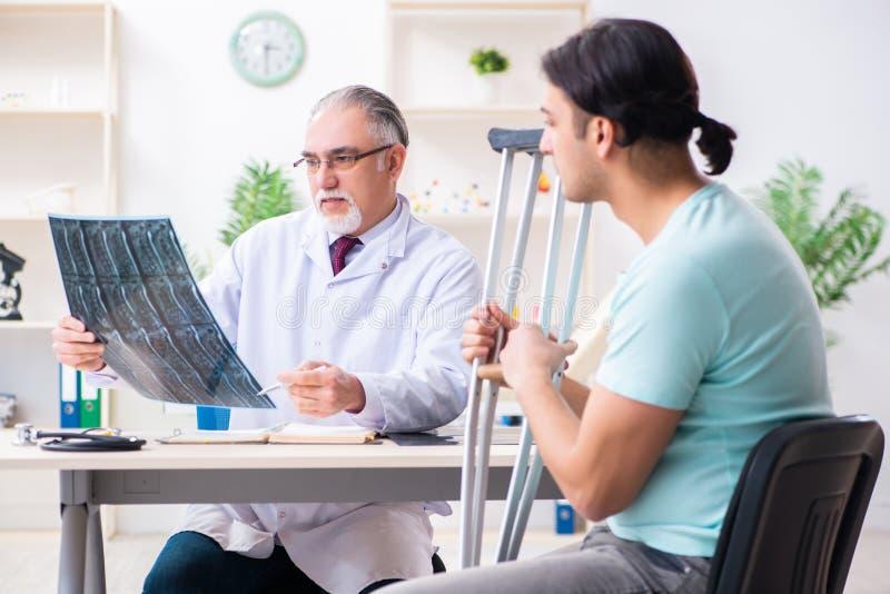 Sårad manlig patient för ungt ben som besöker den gamla doktorn royaltyfri fotografi
