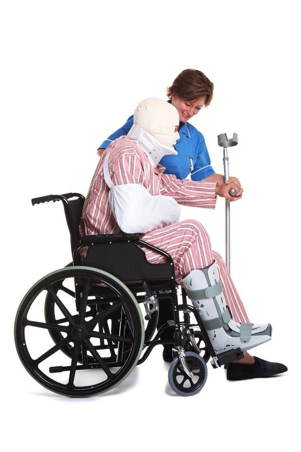 sårad mansjuksköterskarullstol royaltyfri foto