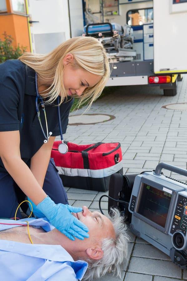 Sårad patient för paramedicinsk portion på gatan royaltyfri foto