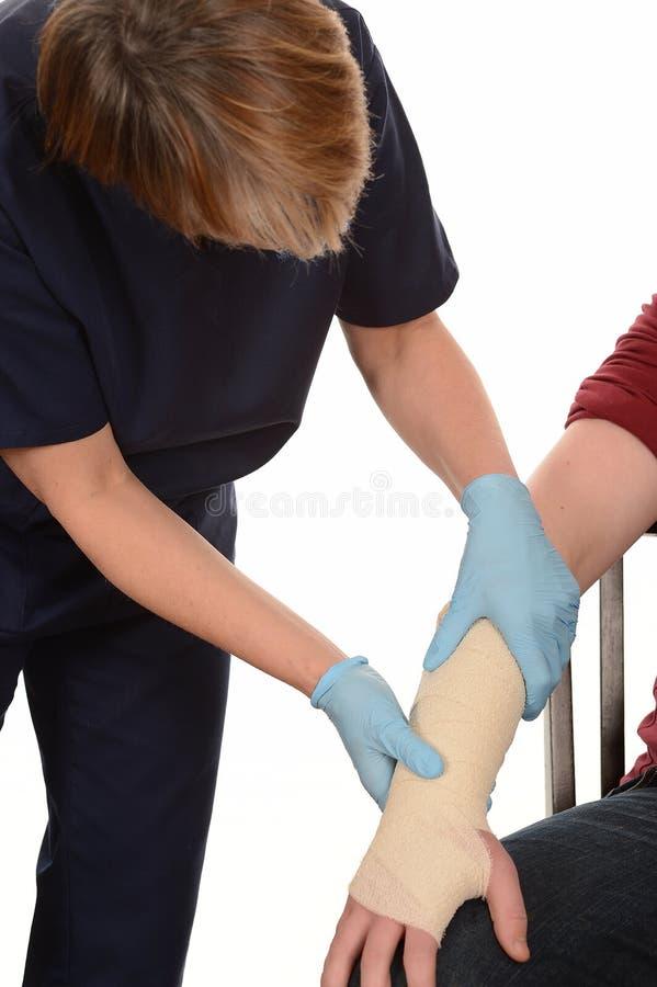 Sårad sjuksköterskabehandling beväpnar royaltyfri foto