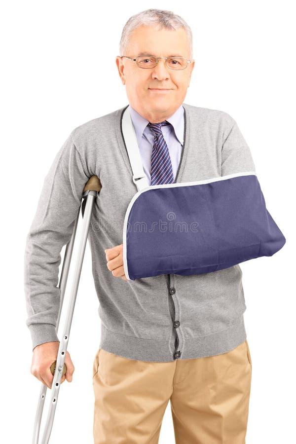 Såradt mogna manen med brutet beväpnar att gå med kryckor arkivfoton