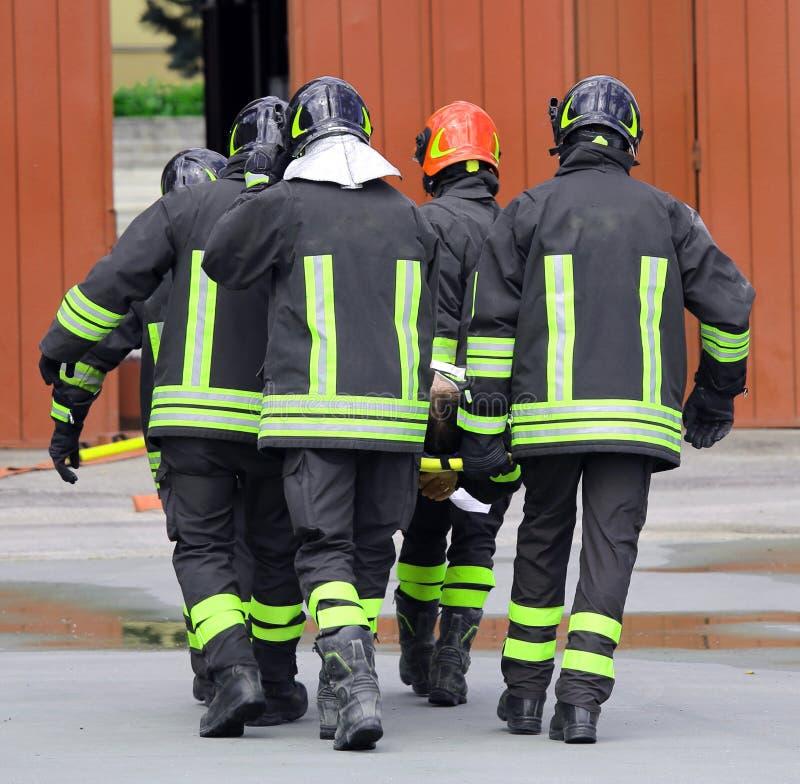 SÅRAT som bärs av brandmän på en bår arkivfoto