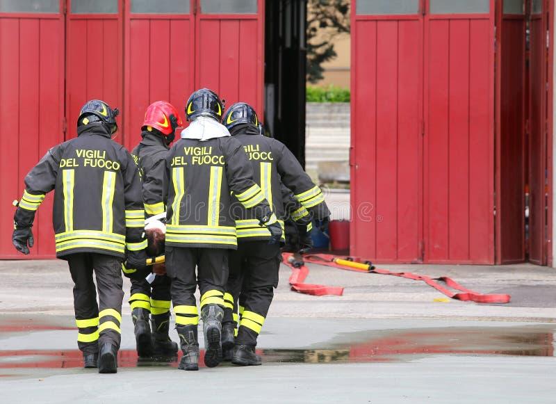 sårat som bärs av brandmän på en bår arkivfoton