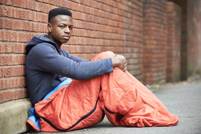 Sårbar tonårs- pojke som sover på gatan arkivfoto