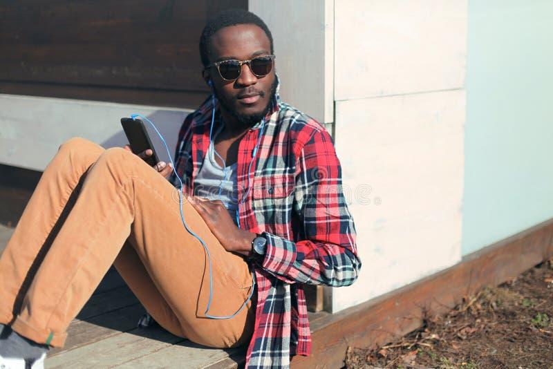 Séance africaine d'homme de portrait de mode la jeune écoute la musique photographie stock