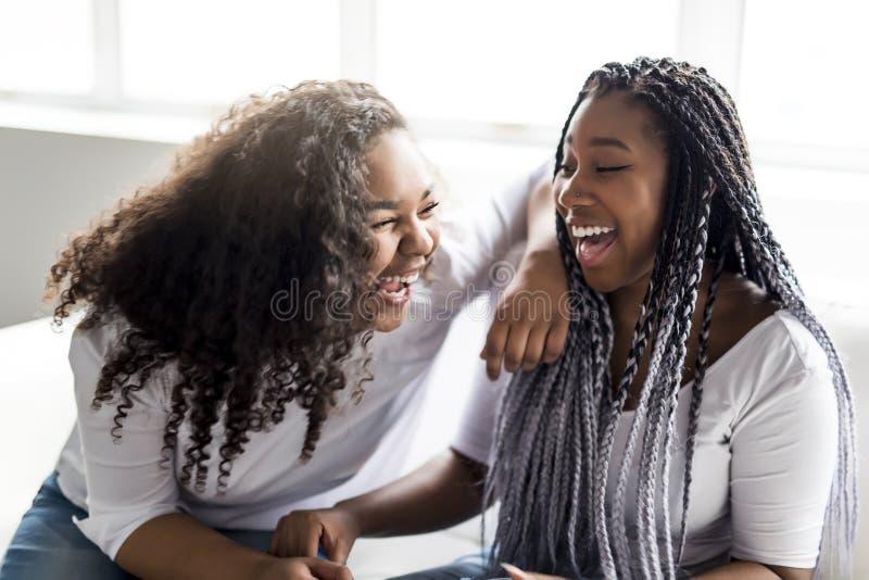 Séance afro-américaine d'amis affectueux sur le sofa photographie stock libre de droits
