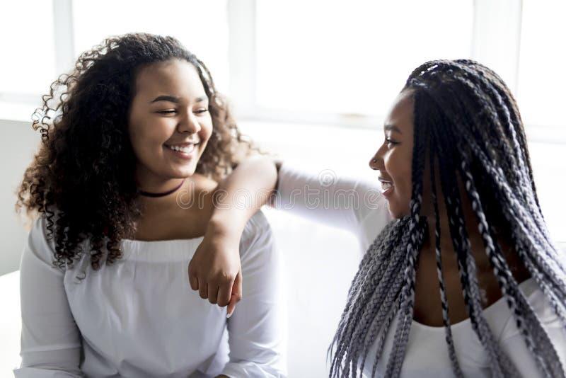Séance afro-américaine d'amis affectueux sur le sofa images libres de droits