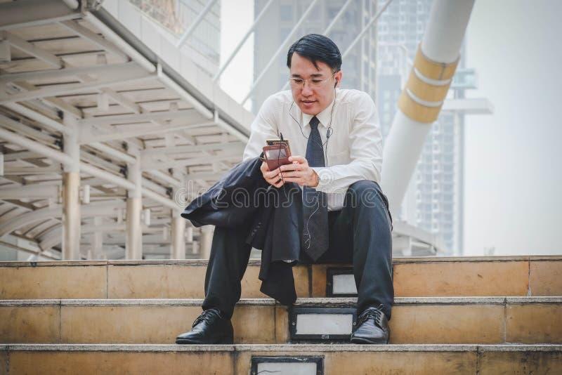 Séance belle d'homme d'affaires et à l'aide des téléphones intelligents image stock