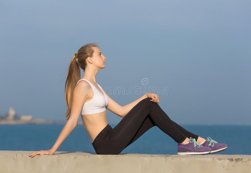 Séance blonde attrayante sur le bord de la mer photo stock