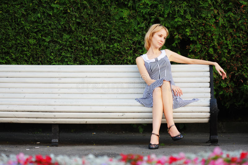 Séance blonde songeuse sur le banc photographie stock libre de droits