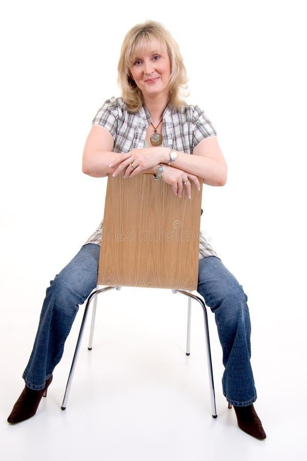Séance blonde sur la présidence photographie stock libre de droits