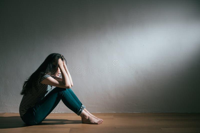 Séance cassée par amour de femme sur pleurer en bois de plancher image stock