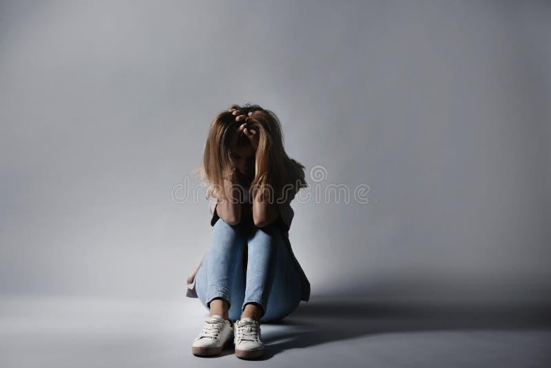 Séance déprimée isolée de femme photographie stock libre de droits