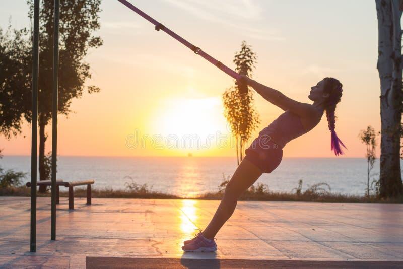 Séance d'entraînement avec des courroies de suspension dans le gymnase extérieur, femme convenable s'exerçant tôt dans le matin s photo stock