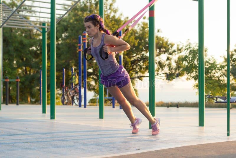 Séance d'entraînement avec des courroies de suspension dans le gymnase extérieur, femme convenable s'exerçant tôt dans le matin s image libre de droits