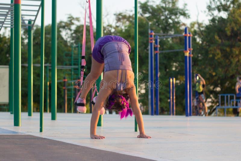 Séance d'entraînement avec des courroies de suspension dans le gymnase extérieur, femme convenable s'exerçant tôt dans le matin s image stock