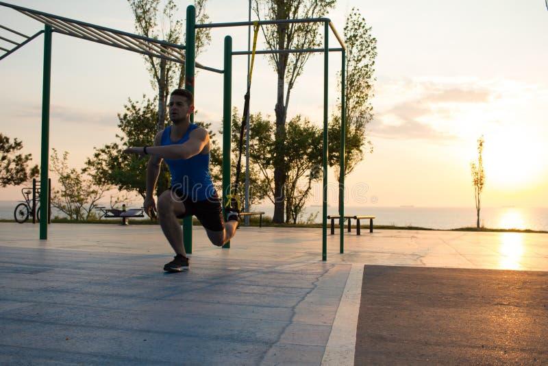 séance d'entraînement avec des courroies de suspension dans le gymnase extérieur, l'homme fort s'exerçant tôt dans le matin sur l photo libre de droits