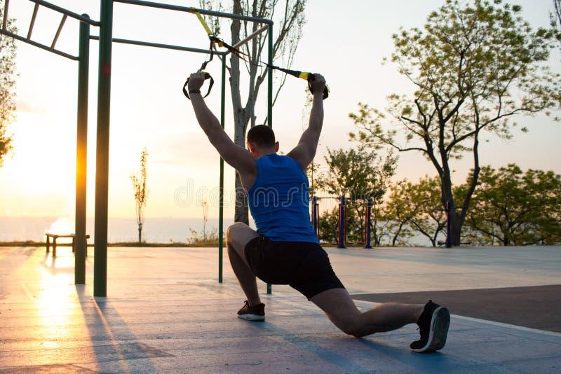 séance d'entraînement avec des courroies de suspension dans le gymnase extérieur, l'homme fort s'exerçant tôt dans le matin sur l photographie stock