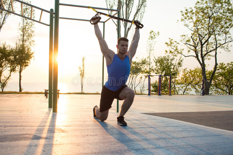 séance d'entraînement avec des courroies de suspension dans le gymnase extérieur, l'homme fort s'exerçant tôt dans le matin sur l photo stock