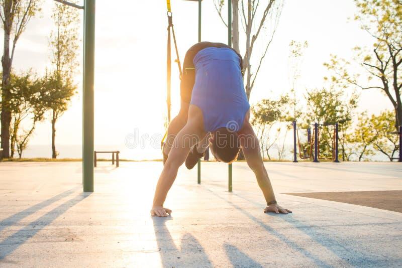 séance d'entraînement avec des courroies de suspension dans le gymnase extérieur, l'homme fort s'exerçant tôt dans le matin sur l photographie stock libre de droits