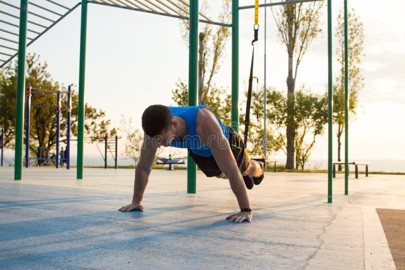 séance d'entraînement avec des courroies de suspension dans le gymnase extérieur, l'homme fort s'exerçant tôt dans le matin sur l photos stock