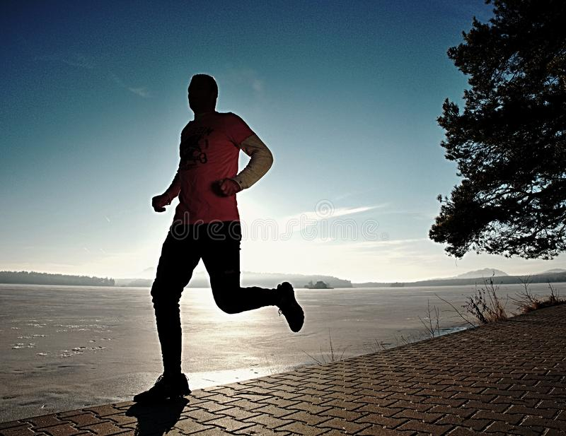 Séance d'entraînement courante d'homme simple, exercice pour la course près du lac congelé photos libres de droits