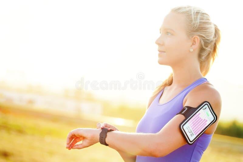 Séance d'entraînement d'arrangement de jeune femme sur la montre intelligente photos stock