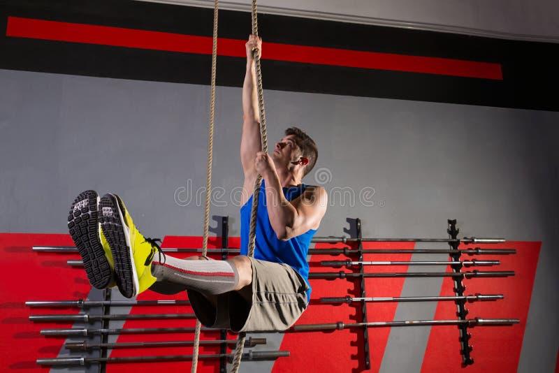 Séance d'entraînement d'homme d'exercice de montée de corde au gymnase photos libres de droits