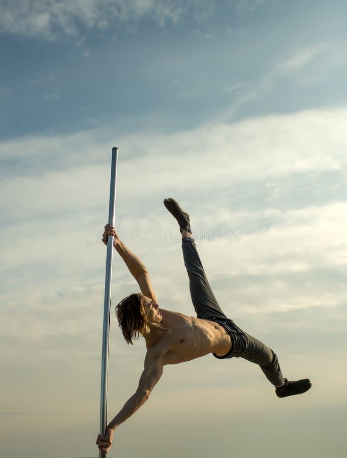 Séance d'entraînement de danseur d'homme fort sur le poteau homme sur le regard de pylône loin sur le ciel bleu photos libres de droits