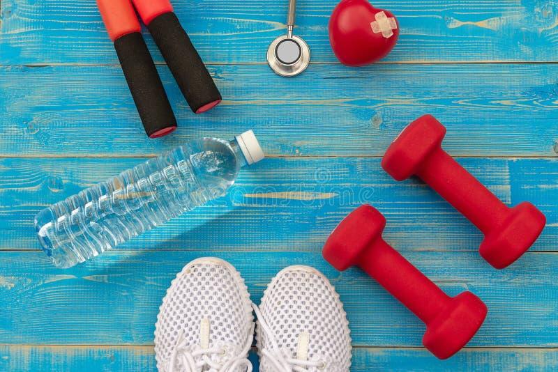 Séance d'entraînement de gymnase d'équipement de forme physique et eau douce avec le coeur et stéthoscope médical sur le fond ble images libres de droits
