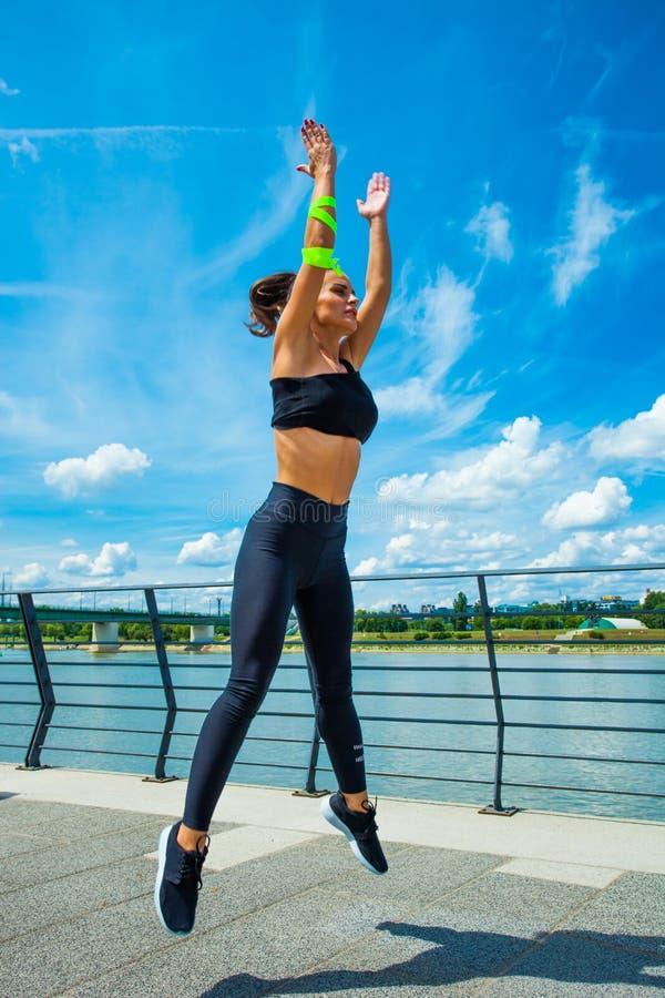Séance d'entraînement de jeune femme sur l'outd sautant de strainght et de construction musculaire photo libre de droits
