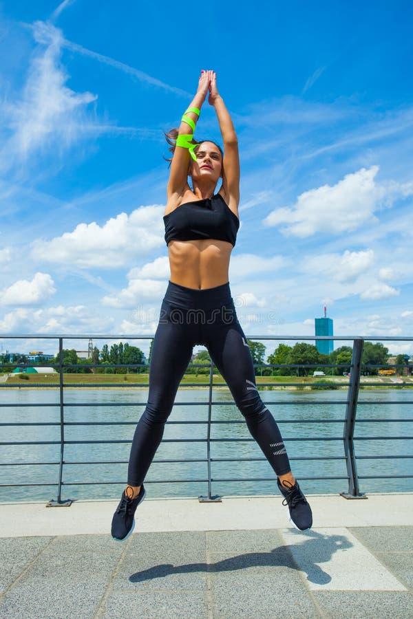 Séance d'entraînement de jeune femme sur l'outd sautant de strainght et de construction musculaire images libres de droits