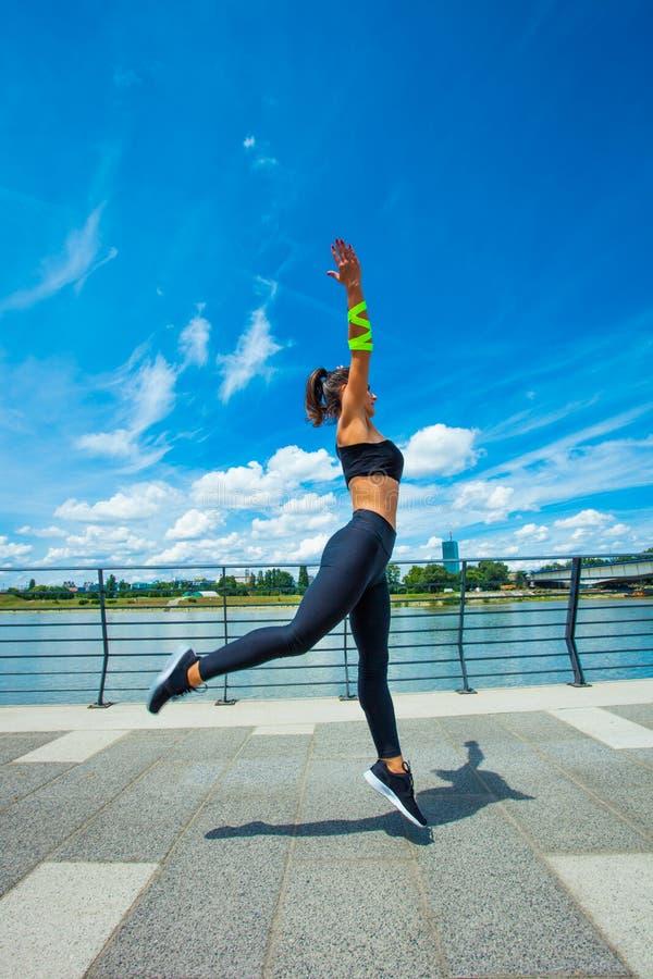 Séance d'entraînement de jeune femme sur l'outd sautant de strainght et de construction musculaire photos stock