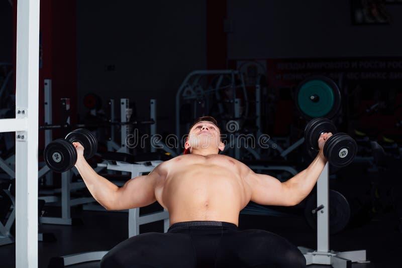 Séance d'entraînement professionnelle de bodybuilder avec le barbell au gymnase Grande formation musculaire sûre d'homme motivati photos stock